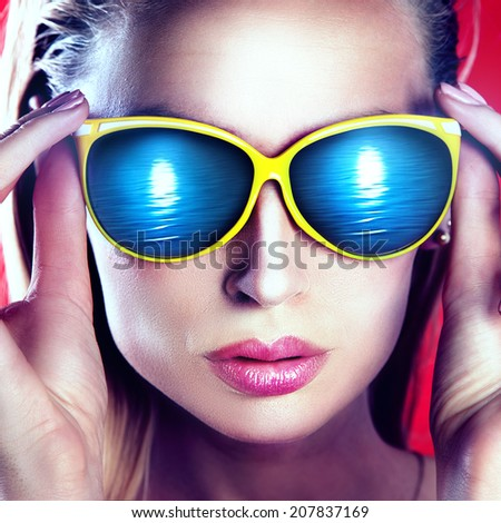 Closeup portrait of beautiful blonde woman wearing fashionable sunglasses.