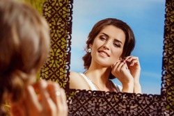 Closeup portrait of beautiful bride putting on ear-ring looking at vintage mirror outdoors at summer background.