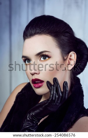 Stock Photo Closeup portrait of beautiful brunette girl. Fashion style. Maroon lips. Black gloves. Beauty make up.