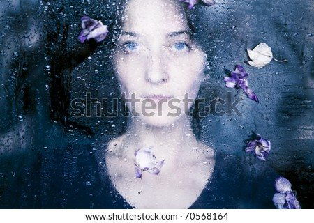 Closeup portrait of beautiful brunette woman behind the window with water drops on it and flowers