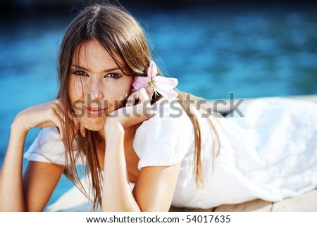 Closeup portrait of beautiful brunette woman with lily in her hair lying on wooden floor near sea - stock photo