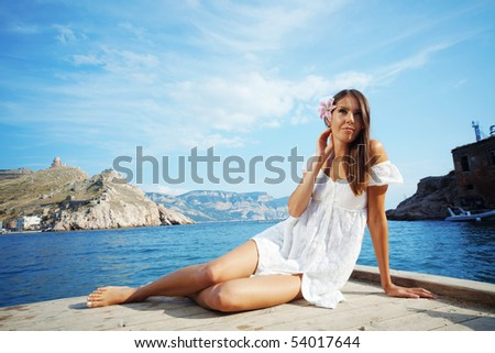 Closeup portrait of beautiful brunette woman with lily in her hair lying on wooden floor near sea