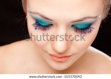 Closeup portrait of beautiful caucasian young woman with blue glamour makeup on black background