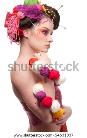 Closeup portrait of beautiful fashion woman with color face art. All in knitting style. Wool balls. Beads