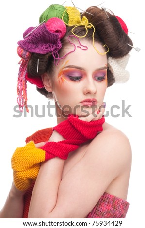 Closeup portrait of beautiful fashion woman with color face art. All in knitting style. Wool balls.