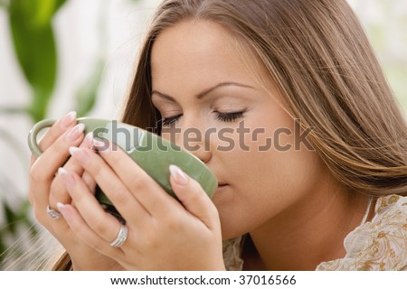 Closeup portrait of beautiful girl drinking tea from green cup.