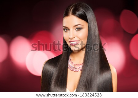 closeup portrait of beautiful girl with straight long dark hair against shining pink background