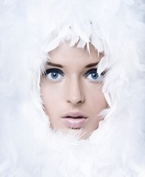 Closeup portrait of beautiful girl with white feathers