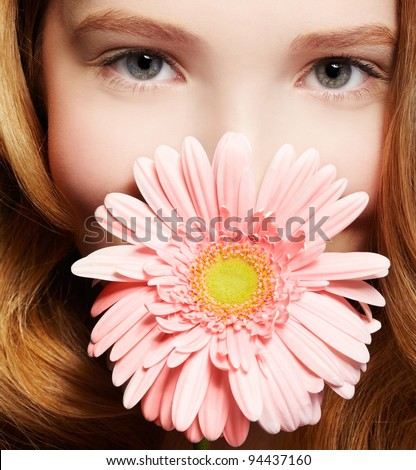 closeup portrait of beautiful healthy redhead teen girl with gerbera flower