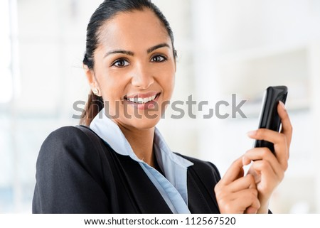 Closeup portrait of beautiful Indian businesswoman sending text message using mobile phone