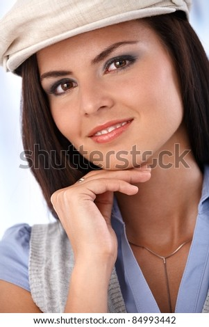 Closeup portrait of beautiful smiling woman in hat, looking at camera.?