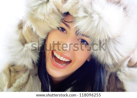 closeup portrait of beautiful smiling young woman in fur
