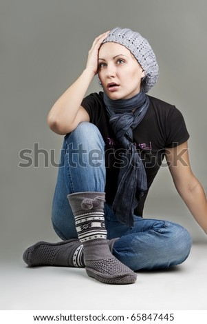 Closeup portrait of beautiful surprised woman sitting comfortably over grey background
