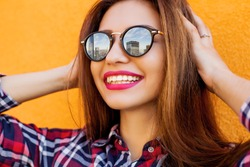 Closeup portrait of beautiful women with perfect make-up and sunglasses with reflection, smiling. Concept target, dream. Archive a goal. Orange background