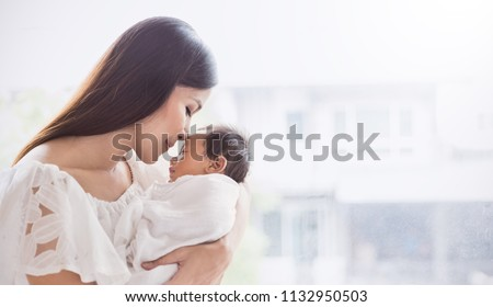 Closeup portrait of beautiful young asian mother kissing her newborn baby. Healthcare and medical family love lifestyle mother's day concept panoramic banner