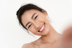 Closeup portrait of beautiful young Asian smilling with white teeth and taking selfie of herself over white wall background. Natural Beauty and Healthy Woman.