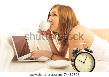 Closeup portrait of beautiful young brunette woman on the bed at home. Working with laptop - stock photo