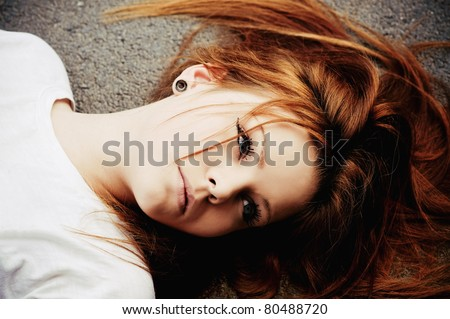 Closeup portrait of beautiful young girl lying on asphalt