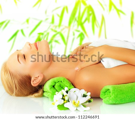 Closeup portrait of beautiful young lady in spa salon, attractive woman sleeping on massage table, side view of girl lying down with closed eyes enjoy dayspa, bamboo background and orchid flower - stock photo