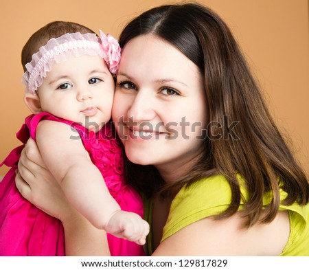 Closeup portrait of beautiful young mother with cute daughter