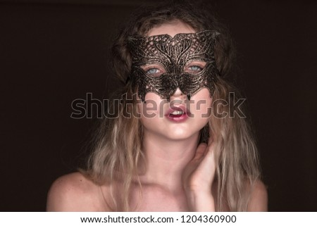 ... cat masquerade mask looking camera. Closeup portrait of beautiful young  tender woman posing isolated over dark beige chocolate brown background wall dec88812976