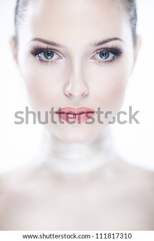 Closeup portrait of beautiful young woman giving the camera a sharp look of intelligence on white background