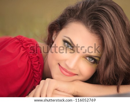 Closeup portrait of beautiful young woman lying on floor and looking at you
