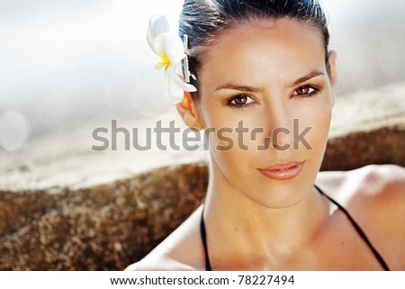 Closeup portrait of beautiful young woman with golden tan resting at beach in summer - stock photo