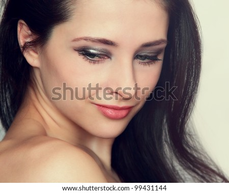 Closeup portrait of beautiful young woman with long hair, makeup attractive face and naked shoulders looking down