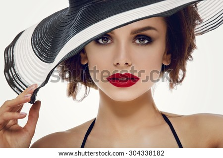 39c8b0f8ad5 Closeup portrait of beautiful young woman with red lips wearing big striped summer  hat. Studio