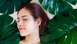 Closeup portrait of beauty asian woman spa green leaf sleeping face perfect healthy glow skin, asian beautiful girl. Beauty clinic skincare organic natural spring earth day environment concept banner