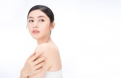 Closeup portrait of beauty asian woman with fair perfect healthy glow skin hand touch shoulder copy space, young beautiful asia girl with pretty smile on face. Beauty korean clinic skincare concept