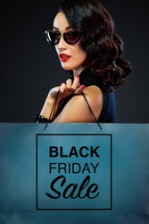 Closeup portrait of black friday sale concept for shop. Woman in sunglasses holding big bag isolated on dark background at shopping.