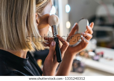 closeup portrait of blond woman who do make up with brush and powder in a room with professional lights. pretty middle age female make up one's face  Сток-фото ©
