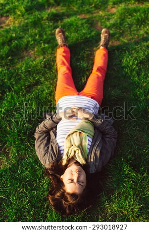 Closeup portrait of brunette girl lying upside down on grass