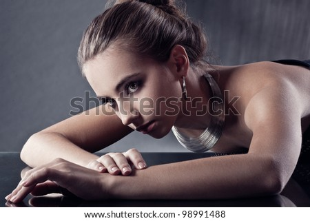 closeup portrait  of brunette woman wearing silver jewellry, specially toned picture