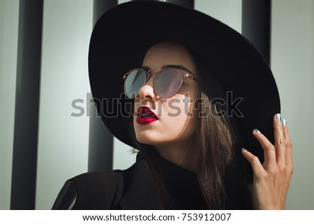 Closeup portrait of brunette woman with bright makeup and shiny hair wears hat and sunglasses