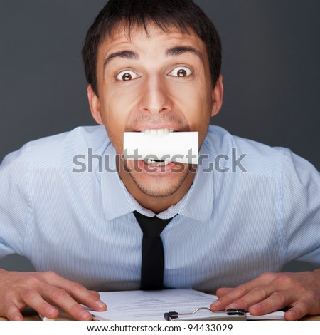 Closeup portrait of business man holding business card in his mouth while sitting at his office.
