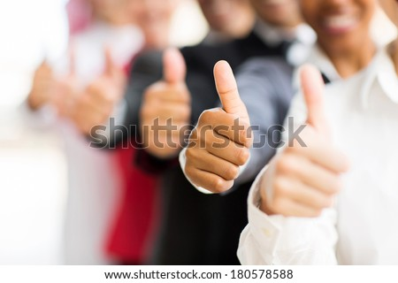 closeup portrait of business people giving thumbs up