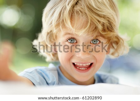 stock photo : Closeup portrait of cheerful little boy with grey eyes smiling