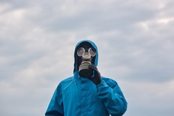 Closeup portrait of chemical scientist or ecologist posing outdoor, dresses blue uniform and respirator, scientist explores surroundings, calls on to protect our environmental. Ecology concept.