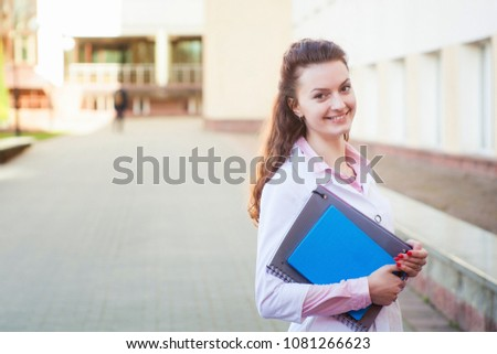 Closeup portrait of confident, smiling female health care professional in white lab coat, isolated background of blurred trees and buildings
