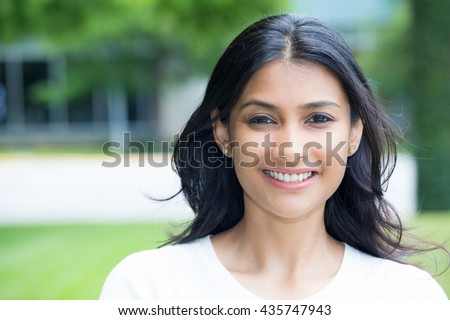 Closeup portrait of confident smiling happy pretty young woman in white shirt, isolated background of blurred trees. Positive human emotion facial expression feelings, attitude, perception