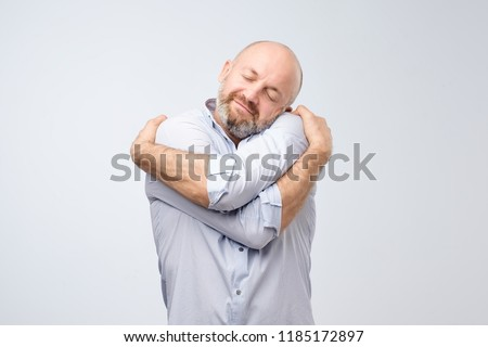 Closeup portrait of confident smiling man holding hugging himself isolated on grey wall background. Positive human emotion, facial expression. Love yourself concept