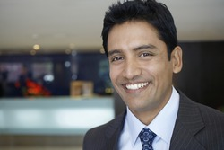 Closeup portrait of confident young businessman smiling in hotel lobby