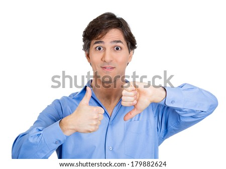 Closeup portrait of confused young man pointing in two different directions, not sure which way to go in life, showing thumbs up, down simultaneously, isolated on white background. Emotion, expression