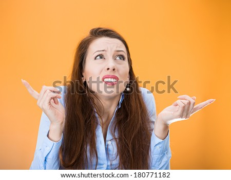 Closeup portrait of confused young woman pointing in two different directions, not sure which way to go in life, isolated on orange background. Negative emotion facial expression feeling body language