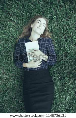 Closeup portrait of content young beautiful woman dozing, embracing book and lying on grass in park. Top view.