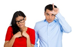 Closeup portrait of couple. Bully husband, man standing  upfront angry, loser sign on head, shy wife, nerdy woman wearing glasses looking downwards, isolated on white background. Human emotion culture