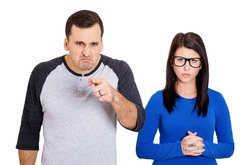 Closeup portrait of couple. Bully husband, man standing upfront, angry, pointing at you and shy wife, nerdy woman wearing glasses standing behind him, isolated on white background. Human emotions